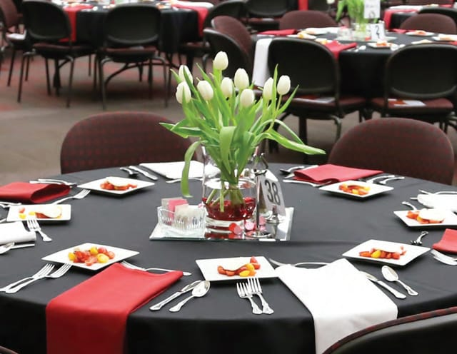 A banquet table set with flowers and place-settings.