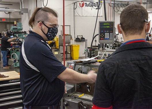 Tulsa Tech graduate David Patrick shows a student a new way to use a machine while taking a tour of the new Manufacturing program space at the Broken Arrow Campus.