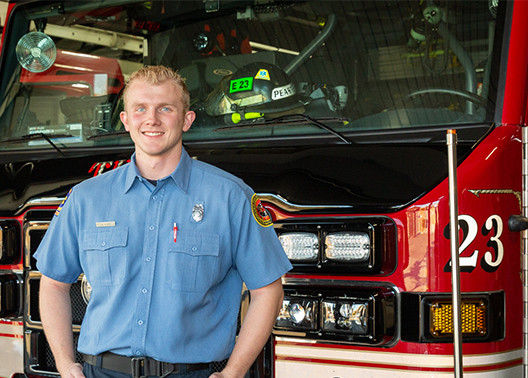 Alumnus smiles in firefighter uniform in front of truck