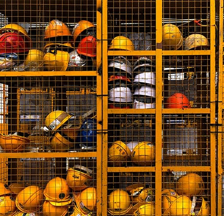 Hardhats stacked in metal storage containers.